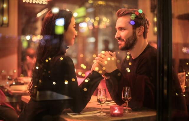 The best winter date idea. Two partners at a restaurant eating dinner.