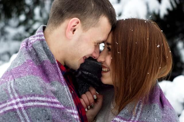 Two people cuddled in a blanket outside during a winter date. You'll love these date ideas for couples.