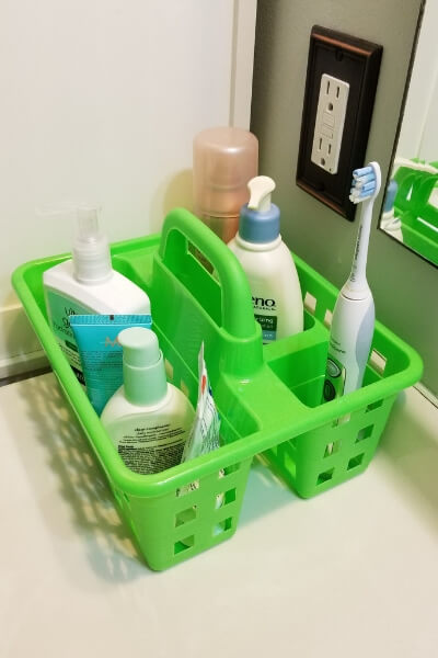Green bin from the Dollar Tree used for bathroom sink organization.