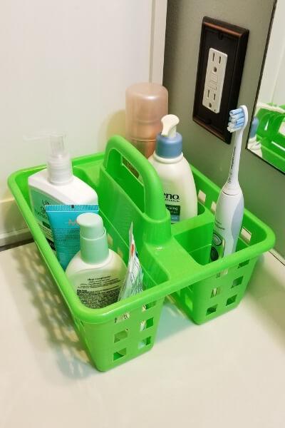 Green bin from the Dollar Tree used for bathroom sink organization.