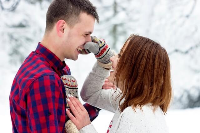 Woman pinching guys nose outside while dating in the winter.