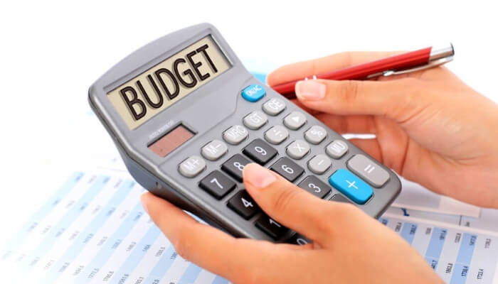 Living in an expensive city budgeting for groceries with a calculator.